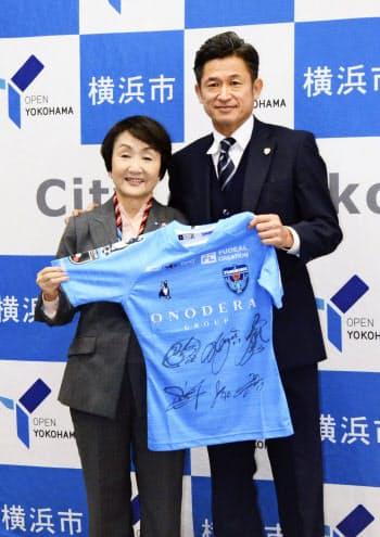 横浜市の林文子市長(左)を表敬訪問し、ユニホームを手渡す横浜FCの三浦知良(3日、横浜市)=共同