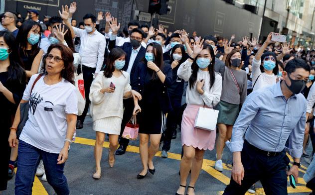 香港の金融街、セントラルでは昼休みに銀行、証券会社などで働く高収入のエリートらがマスク姿で「ランチタイムデモ」に参加している(11月25日)=ロイター