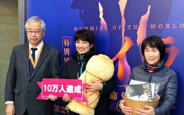 「10万人突破」の記念品を贈られた山口沙織さん(中)