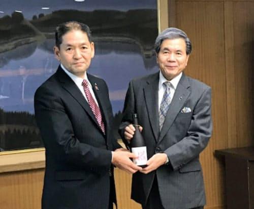 益城ブランド焼酎が完成し、西村益城町長(左)が蒲島熊本知事に贈呈した(3日、熊本市)