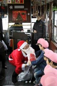 車内ではサンタクロースにふんした社員がお菓子の詰め合わせをプレゼントした(3日、岡山市)