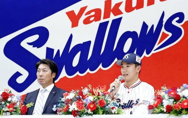 ヤクルトの入団記者会見で、質問に答えるドラフト1位の奥川恭伸投手。左は高津監督(3日午後、東京都港区)=共同