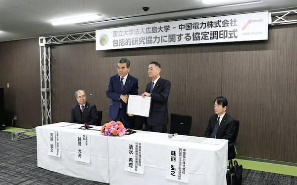 中国電力と広島大学は技術開発や研究などで協力する包括協定を結んだ(4日、広島市、右=中国電の清水社長、左=広島大の越智学長)
