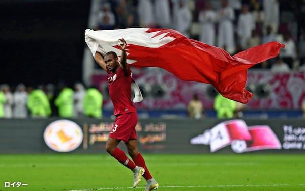 2日、UAEとのサッカーの試合に勝利し、国旗を振って喜ぶカタールの選手=ロイター