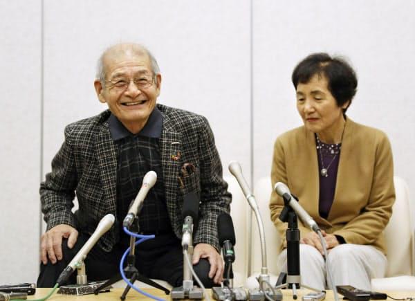 ノーベル賞授賞式への出発を前に、記者会見する吉野彰さん。右は妻の久実子さん(5日午前、成田空港)=共同