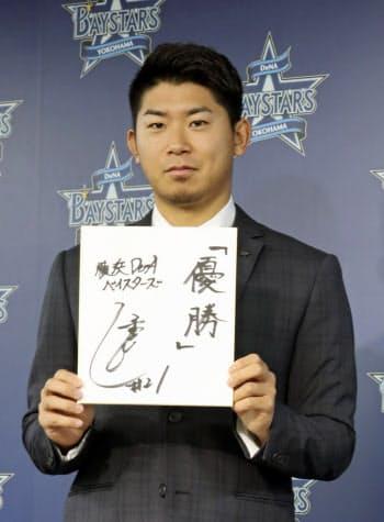契約更改後に記者会見で、来期の抱負を記した色紙を手にポーズをとるDeNAの今永(5日、横浜市の球団事務所)=共同