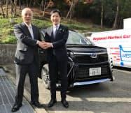 相乗りサービスに使う車両の前で握手する四宮慶太郎・ネッツ神戸社長(右)と福田長治・猪名川町長