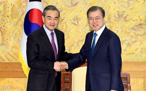 韓国の文大統領と握手する中国の王毅外相(左)(5日、ソウル)=ロイター