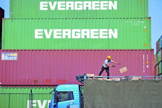 米中貿易は関税で縮小している(中国山東省青島市の港で輸入品を積み込む作業員)=AP