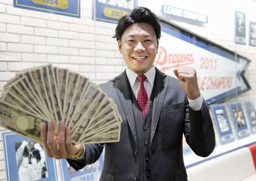 報道陣から渡された、お札をデザインしたトランプを手に笑顔でポーズをとる中日・大野雄(6日、名古屋市の球団事務所)=共同