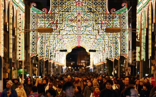 開幕した「神戸ルミナリエ」で光の作品の下を歩く来場者(6日夜、神戸市中央区)