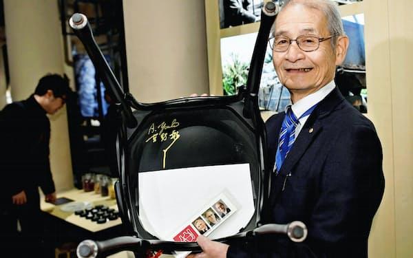 ストックホルムのノーベル博物館でサインした椅子を持つ吉野彰・旭化成名誉フェロー=6日(ロイター=共同)