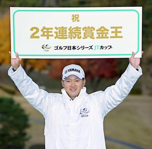 2年連続の賞金王となり、ボードを掲げる今平周吾(8日、東京よみうりCC)=共同