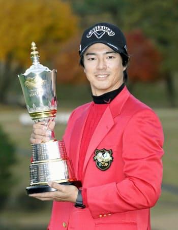 通算17勝目を挙げ、トロフィーを手に笑顔の石川遼。史上最年少で生涯獲得賞金10億円に達した(8日、東京よみうりCC)=共同