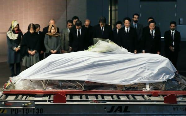 アフガニスタンで殺害された中村医師の遺体が納められたひつぎの前で、黙とうする妻の尚子さん(前列左端)と長女の秋子さん(同2人目)ら関係者(8日、成田空港)
