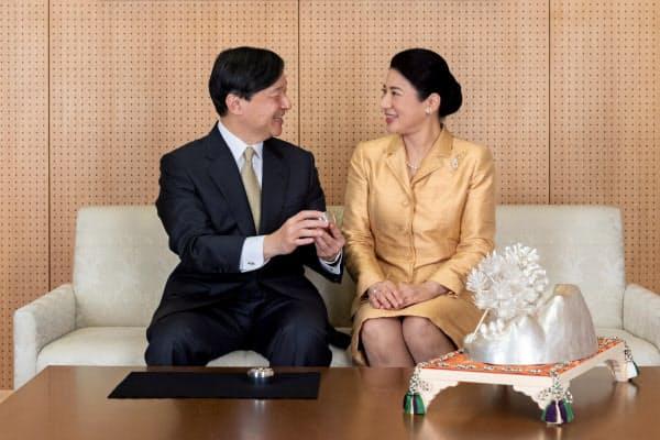 饗宴の儀で参列者に記念品として配られたボンボニエールを手に取って話す天皇、皇后両陛下(12月3日、東京・港の赤坂御所)=宮内庁提供
