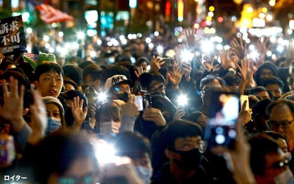 5本の指をあげて「五大要求」を訴える人たち(8日、香港)=ロイター