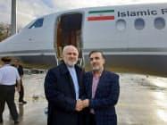 釈放された科学者(右)と握手するイランのザリフ外相(7日、チューリヒ、イラン外相のツイッターから)=AP