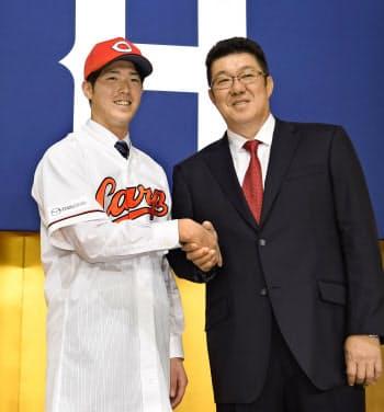 広島の新人入団記者会見で、佐々岡新監督(右)と握手する森下暢仁投手(9日、広島市)=共同