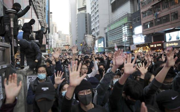 手のひらを広げて「五大要求」を訴える人たち。香港政府との対立は長期戦の様相を強めている(8日、香港)=AP