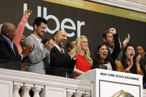 米ニューヨーク証券取引所で上場を祝うウーバー・テクノロジーズの関係者ら(5月)=AP