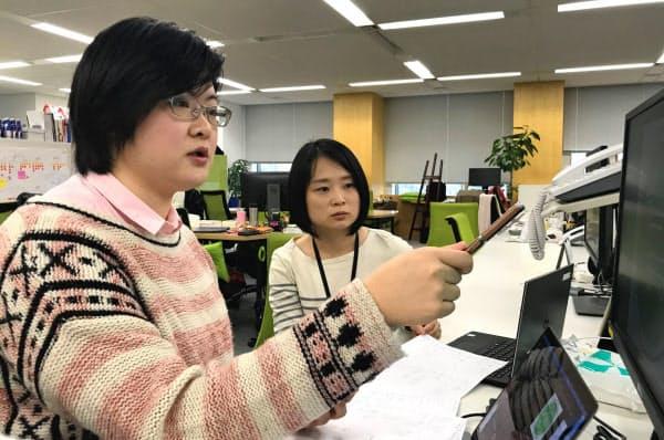 日本のIT大手で働く香港出身の楊さん(左)は「給料は香港の方が高い」と話す(東京・新宿)