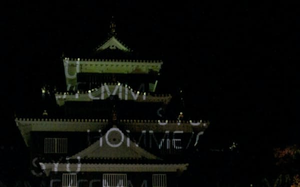 岡山城をバックにデニム生地のランウエーでポーズを決める冨永さん(7日、岡山市)
