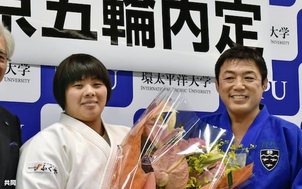 岡山市の環太平洋大で花束を贈られ笑顔の素根輝。右は総監督を務める古賀稔彦氏(9日)=共同
