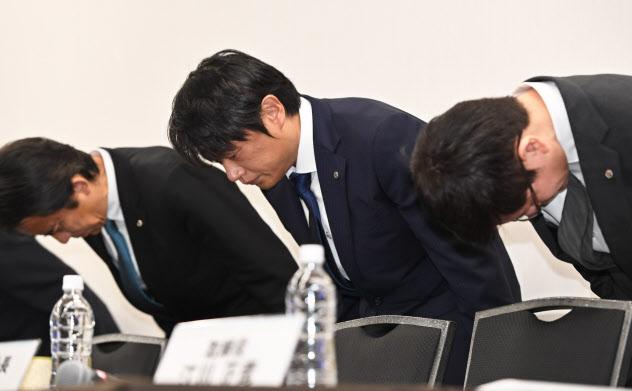 記者会見で頭を下げるブロードリンクの榊彰一社長(中)(9日、東京都千代田区)
