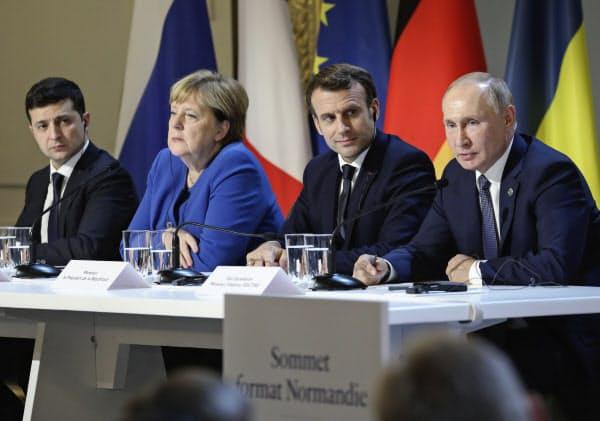 会談を終え記者会見する(左から)ウクライナのゼレンスキー大統領、ドイツのメルケル首相、フランスのマクロン大統領、ロシアのプーチン大統領(9日、パリ)=AP