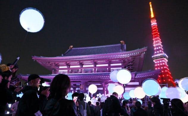 音楽に合わせて光るバルーンを手に光のアートを楽しむ(11月16日、東京都港区の増上寺)