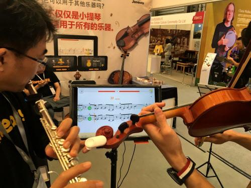 バイオリンに付けた小型センサー端末が演奏の音を読み取って、音階やリズムの間違いを指摘する(ジェムイージーのサービス)