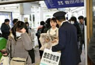 清水愛美さん殺害事件の情報提供を呼び掛ける愛知県警の警察官(10日午前、名鉄豊田市駅)=共同