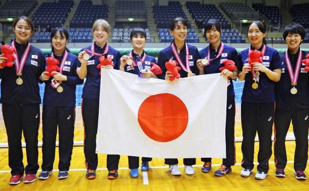 アジアパシフィック選手権で優勝し、金メダルを掲げる日本女子選手ら(10日、千葉ポートアリーナ)=共同