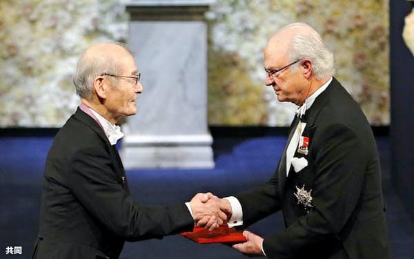 スウェーデンのカール16世グスタフ国王(右)からノーベル化学賞のメダルと賞状を授与される吉野彰・旭化成名誉フェロー(10日、ストックホルム)=共同