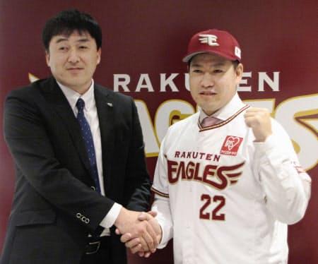 楽天の入団記者会見で石井GM(左)と握手する牧田和久投手(11日、楽天生命パーク宮城)=共同
