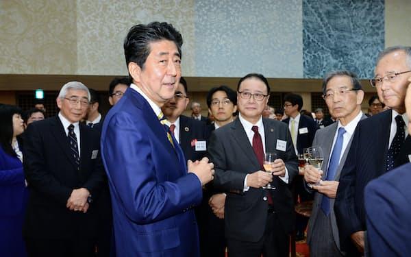 年末エコノミスト懇親会で歓談する安倍首相                                                       ら(11日、東京都港区)
