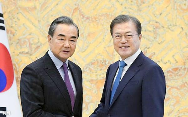 中国はTHAAD問題を蒸し返した。5日、ソウルの大統領府で握手する韓国の文在寅大統領(右)と中国の王毅外相(韓国大統領府提供・共同)