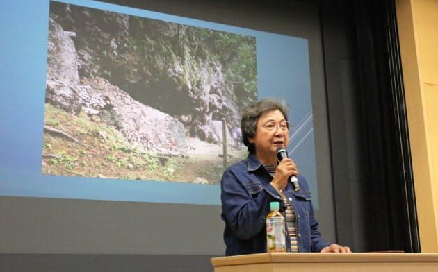 墳墓の写真を示し、沖縄の人々の死生観を語る原告の亀谷正子さん(11月28日、京都市)