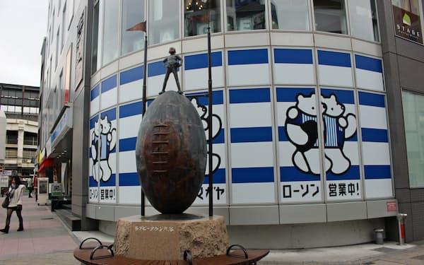 モニュメント「ラグビーボールと少年」の後ろには「スクマム!クマガヤ」のロゴマークとローソンがコラボしたポスターがある