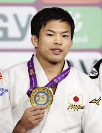 男子60キロ級で優勝し、金メダルを手に笑顔の永山竜樹(12日、青島)=共同
