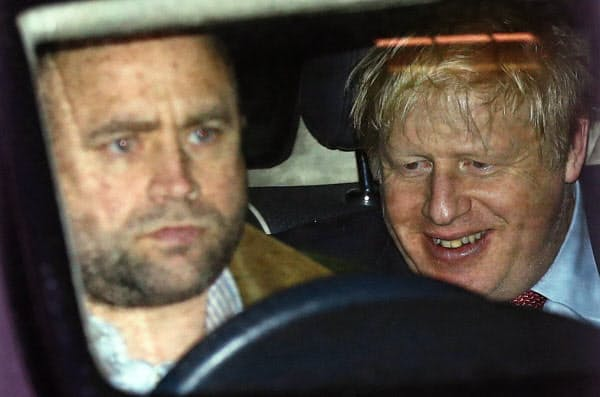 13日、保守党本部を出るジョンソン首相=ロイター