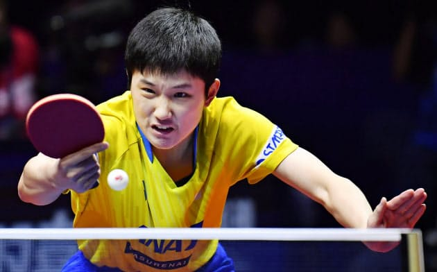 男子シングルス準々決勝でプレーする張本(13日、鄭州)=共同