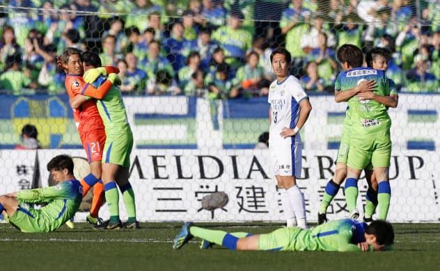 J1残留を決め、抱き合って喜ぶ湘南イレブン。中央右はぼうぜんとする徳島・清武(14日、BMWスタジアム)=共同