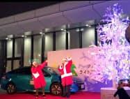 電動車の電源を使いツリーを点灯した河合副社長(右、14日、名古屋市)