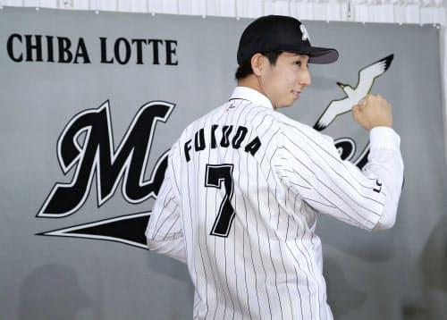 ロッテの入団会見で背番号を見せ、ポーズをとる福田秀平外野手(15日午後、千葉市内のホテル)=共同
