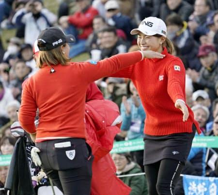 団体対抗戦で優勝し、抱き合う渋野日向子(右)と鈴木愛(15日、グリッサンドGC)=共同