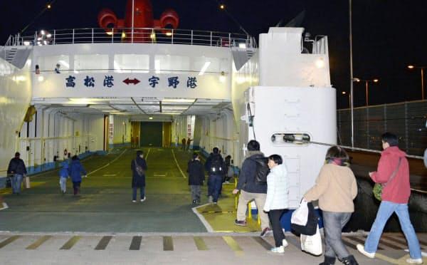 高松港で「宇高航路」の最終便となるフェリーに乗り込む乗客(15日夜、高松市)=共同