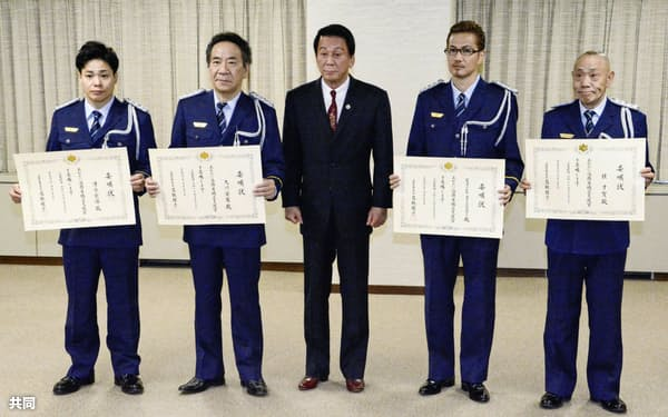 矯正支援官の委嘱状を交付された「EXILE」のATSUSHIさん(右から2人目)ら。中央は特別矯正監を委嘱されている杉良太郎さん(12日午後、法務省)=共同