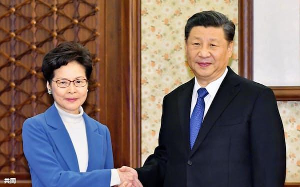 握手する中国の習近平国家主席(右)と香港政府トップの林鄭月娥行政長官(16日、北京)=香港政府提供・共同